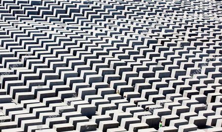 People walk through the concrete blocks of the the Holocaust memorial in Berlin, Germany, . The memorial to the 6 million Jews killed in Europe under the Nazis was created by U.S. architect Peter Eisenman and consists of an undulating field of 2,711 blocks through which visitors can wander