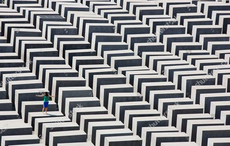 A woman stands on a concrete stele of the the Holocaust memorial in Berlin, Germany, . The memorial to the 6 million Jews killed in Europe under the Nazis was created by U.S. architect Peter Eisenman and consists of an undulating field of 2,711 steles through which visitors can wander