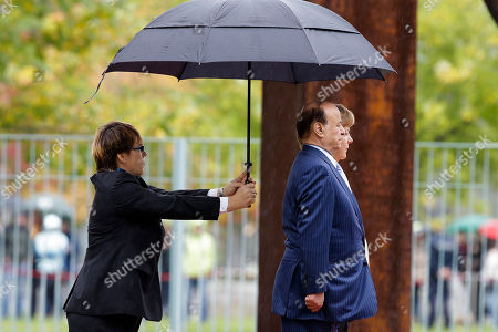 Angela Merkel, Abd Rabbuh Mansur Al-Hadi German Chancellor Angela Merkel, rear, and the President of the Yemen Abd Rabbuh Mansur Al-Hadi, center, stand under an umbrella as they listen to the national anthems prior to talks at the chancellery in Berlin, Germany