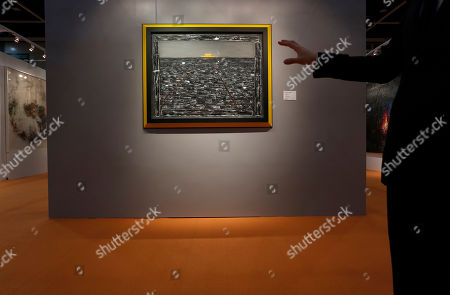"A man gestures in front of a painting titled ""Tiananmen No. 1"" by Chinese artist Zhang Xiaogang during Sotheby's auction press preview in Hong Kong . The work, estimated at US$1.9 million to 3.2 million, will be auctioned as part of the autumn sale"