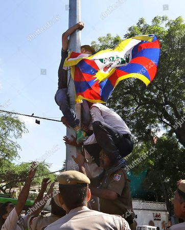 Police and traffic officials pull down a Tibetan exile who climbed a streetlight post holding a Tibetan flag, during a protest against the visit of Chinese Defense Minister Liang Guanglie in New Delhi, India, . The defense ministers of India and China agreed Tuesday to resume joint military exercises frozen two years ago, signaling a thaw between the Asian giants even as regional relations are tense over the disputed South China Sea