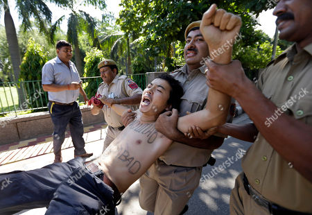 Indian policemen detain a Tibetan exile shouting slogans during a protest against the visit of Chinese Defense Minister Liang Guanglie in New Delhi, India, . The defense ministers of India and China agreed Tuesday to resume joint military exercises frozen two years ago, signaling a thaw between the Asian giants even as regional relations are tense over the disputed South China Sea