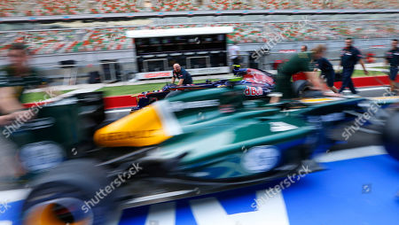 Mechanics push Caterham driver Vitaly Petrov of Russia's car, front, and Toro Rosso driver Jean-Eric Vergne of France's car down pit lane ahead of the Indian Formula One Grand Prix at the Buddh International Circuit in Noida, on the outskirts of New Delhi, India