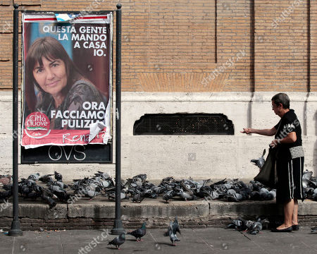 """Marinella Schiavone, a retired professor of philosophy, feeds pigeons near a poster of Lazio Region governor Renata Polverini reading in Italian: """"I send these people home. Now let's clean up"""" in Rome, . Polverini, of former premier Silvio Berlusconi's PDL People of Freedom party, resigned as governor of Lazio Monday over an alleged corruption and misuse of public funds scandal involving regional politicians of PDL"""