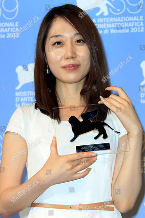 Wang Bing Yoo Min-young poses with Orizzonti Award for Best Short Film for ' Cho-De' at the awards photo call during the 69th edition of the Venice Film Festival in Venice, Italy