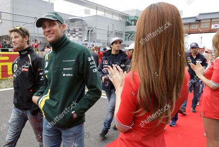 Lotus driver Romain Grosjean of France walks with Caterham driver Vitaly Petrov of Russia along pit lane during the drivers parade prior to the start of the Korean Formula One Grand Prix at the Korean International Circuit in Yeongam, South Korea