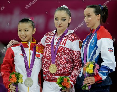 Russian gold medallist gymnast Aliya Mustafina, center, Chinese silver medallist He Kexin, left, and Britain's bronze medallist Elizabeth Tweddle stand during the podium ceremony for the uneven bars during the artistic gymnastics women's apparatus finals at the 2012 Summer Olympics, in London