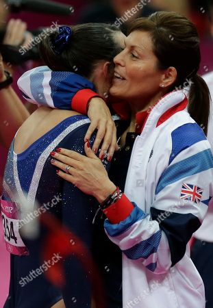Britain's gymnast Elizabeth Tweddle, left, hugs her coach after performing on the uneven bars during the artistic gymnastics women's apparatus finals at the 2012 Summer Olympics, in London