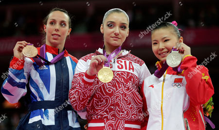 Russian gold medallist gymnast Aliya Mustafina, center, Chinese silver medallist He Kexin, right, and Britain's bronze medallist Elizabeth Tweddle display their medals for the uneven bars during the artistic gymnastics women's apparatus finals at the 2012 Summer Olympics, in London