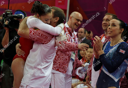 Russian gymnast Aliya Mustafina, left, is hugged by her coach as Britain's gymnast Elizabeth Tweddle, right, applauds after final results for the uneven bars were declared during the artistic gymnastics women's apparatus finals at the 2012 Summer Olympics, in London