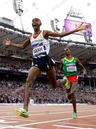 Britain's Mo Farah reacts as he crosses the finish line to win gold in the men's 5000-meter final ahead of Ethiopia's Dejen Gebremeskel during the athletics in the Olympic Stadium at the 2012 Summer Olympics, London