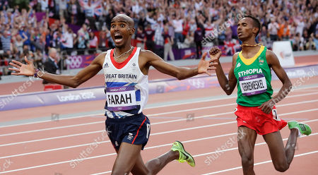 Britain's Mo Farah, left, reacts as he crosses the finish line to win gold in the men's 5000-meter final ahead of Ethiopia's Dejen Gebremeskel during the athletics in the Olympic Stadium at the 2012 Summer Olympics, London