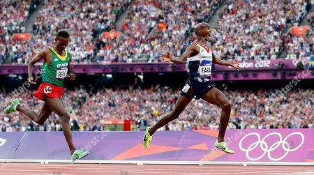 Britain's Mo Farah, right, reacts as he goes to cross the finish line ahead of Ethiopia's Dejen Gebremeskel to win gold in the men's 5000-meter final during the athletics in the Olympic Stadium at the 2012 Summer Olympics, London