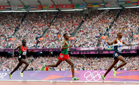 Britain's Mo Farah, right, reacts as he goes to cross the finish line ahead of Ethiopia's Dejen Gebremeskel, center, and Kenya's Thomas Pkemei Longosiwa to win gold in the men's 5000-meter final during the athletics in the Olympic Stadium at the 2012 Summer Olympics, London