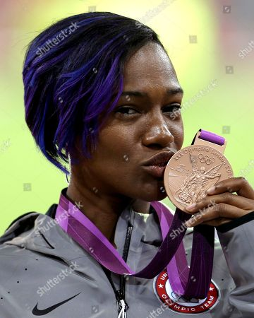 United States' Kellie Wells kisses her bronze medal for the women's 100-meter hurdles during the athletics in the Olympic Stadium at the 2012 Summer Olympics, London