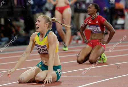 Australia's Sally Pearson, left, reacts after winning gold in the women's 100-meter hurdles final as bronze medallist United States' Kellie Wells is seen in the background, during the athletics in the Olympic Stadium at the 2012 Summer Olympics, London