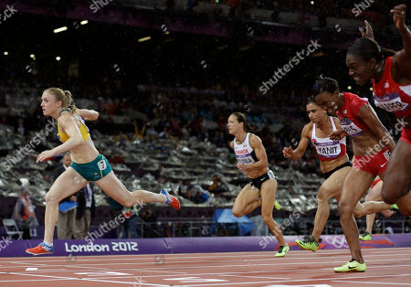 Australia's Sally Pearson, left, crosses the finish line to win gold ahead of United States' Dawn Harper, right, United States' Kellie Wells, second from right, Canada's Jessica Zelinka, second from left, and Turkey's Nevin Yanit in the women's 100-meter hurdles finalduring the athletics in the Olympic Stadium at the 2012 Summer Olympics, London