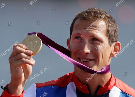 Great Britain's Ed McKeever displays the gold medal he won in the men's kayak single 200m in Eton Dorney, near Windsor, England, at the 2012 Summer Olympics