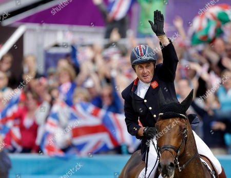 Peter Charles, of Great Britain, waves to the fans after riding Vindicat to a gold medal during the equestrian show jumping team competition at the 2012 Summer Olympics, in London