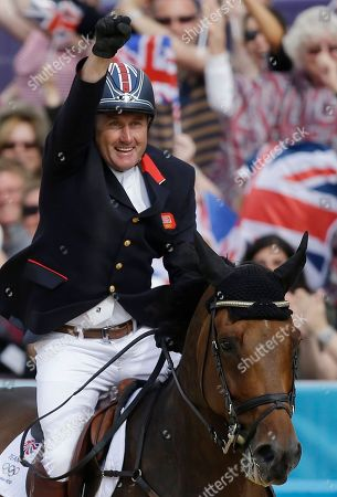 Peter Charles, of Great Britain, reacts after riding Vindicat to a gold medal during the equestrian show jumping team competition at the 2012 Summer Olympics, in London