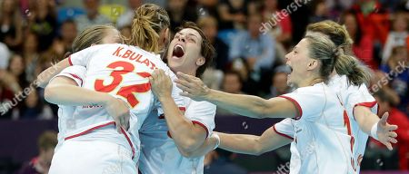 Montenegro's Katarina Bulatovic (32) embraces team mate Ana Dokic after scoring and defeating France in their women's handball quarterfinal match at the 2012 Summer Olympics, in London