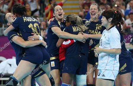 South Korea's Woo Sun-hee, right, walks past players of Spain celebrating their victory in the women's handball bronze medal match against at the 2012 Summer Olympics, in London