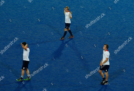 Britain's Ashley Jackson, top, James Tindall, left, and Matt Daly walk off the field after loosing to the Netherlands in a men's field hockey semifinal match at the 2012 Summer Olympics, in London