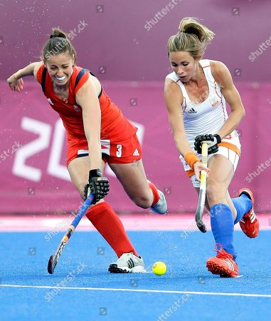 Britain's Emily Maguire, left, and the Netherlands' Ellen Hoog vie for the ball during a preliminary round women's hockey match at the Riverside Arena at the 2012 Summer Olympics, London