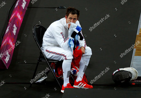 Nicholas Woodbridge of Britain wipes his face with a towel during the men's fencing section of the modern pentathlon at the 2012 Summer Olympics, in London