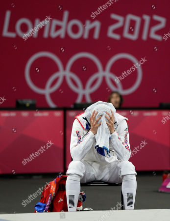 Nicholas Woodbridge of Britain uses his towel during the fencing section of the men's modern pentathlon at the 2012 Summer Olympics, in London