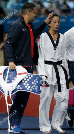 United States' Diana Lopez walks with her coach Jean Lopez, left, after losing to Finland's Suvi Mikkonen in women's 57-kg taekwondo competition at the 2012 Summer Olympics, in London