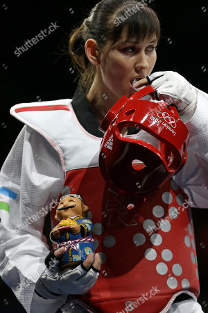 Uzbekistan's Natalya Mamatova holds a handmade doll before presenting it to France's Anne-Caroline Graffe prior to their match in women's plus 67-kg taekwondo competition at the 2012 Summer Olympics, in London