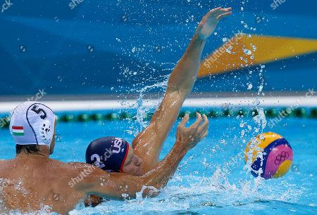 Peter Varellas, right, of the United States, struggles to get the ball away from Tamas Kasas of Hungary during their men's water polo preliminary round match at the 2012 Summer Olympics, in London