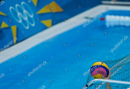 Merrill Moses of the United States reaches out to grab the ball from the back of the net after Spain scored a goal during their men's semifinal fifth to eighth place water polo match at the 2012 Summer Olympics, in London