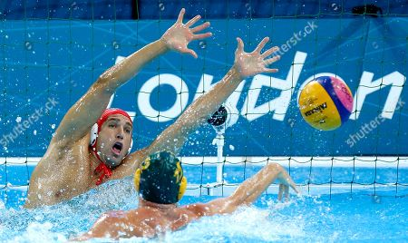 Gavin Woods, right, of Australia shoots and scores a gaol past the outstretched hands of goalkeeper Merrill Moses of the United States during the men's water polo seventh place match at the 2012 Summer Olympics, in London