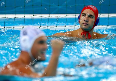 Norbert Hosnyanszky, Merrill Moses United States goalkeeper Merrill Moses, top, looks on as Norbert Hosnyanszky of Hungary celebrates after scoring a goal during a preliminary men's water polo match at the 2012 Summer Olympics, in London. Hungary won 11-6