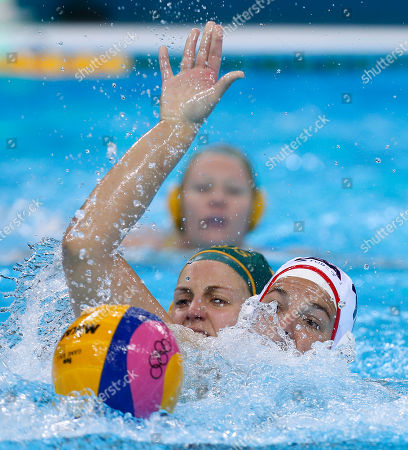 Kami Craig of the United States, right reaches out to gather the ball under pressure from Rowie Webster of Australia during their women's semifinal water polo match at the 2012 Summer Olympics, in London