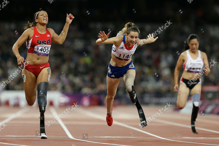 Stock Photo of France's Marie-Amelie Le Fur, center, crosses the finish line to win gold in the women's 100m T44 final, seen left, is April Holmes of the United States, at the 2012 Paralympics, in London