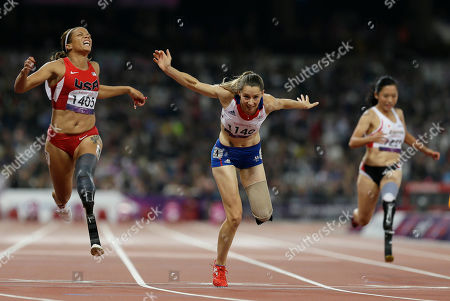 France's Marie-Amelie Le Fur, center, crosses the finish line to win gold in the women's 100m T44 final, seen left, is April Holmes of the United States, at the 2012 Paralympics, in London