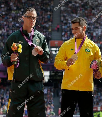Brazil's Alan Fonteles Cardoso Oliveira with the gold, right, looks towards South Africa's Oscar Pistorius with the silver, left, at the medal ceremony for the men's 200m T44 at the 2012 Paralympics, in London