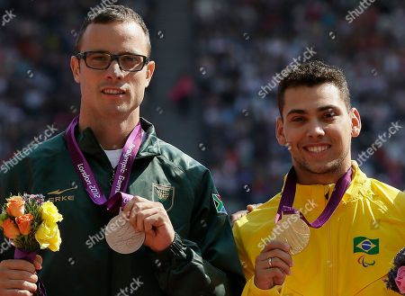 South Africa's Oscar Pistorius with the silver, left, and Brazil's Alan Fonteles Cardoso Oliveira with the gold, right, at the medal ceremony for the men's 200m T44 at the 2012 Paralympics, in London