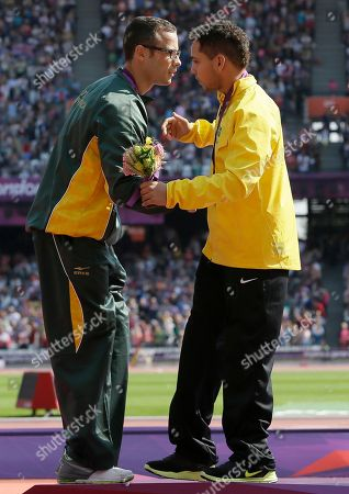 South Africa's Oscar Pistorius with the silver, left, leans to hug Brazil's Alan Fonteles Cardoso Oliveira with the gold, right, at the medal ceremony for the men's 200m T44 at the 2012 Paralympics, in London