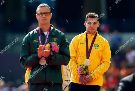 Gold medal winner Brazil's Alan Oliveira, right, stands beside silver medalist South Africa's Oscar Pistorius after listening to his country's national anthem in the medal ceremony for the men's 200m T44 category final during the athletics competition at the 2012 Paralympics, in London. Pistorius, who won a legal battle to compete wearing carbon-fiber blades alongside able-bodied runners at the Olympics last month, suggested after the race that Oliveira ran with longer prosthesis than should be allowed