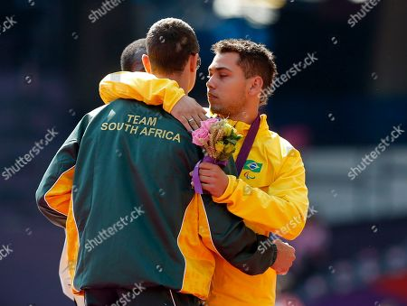 Gold medal winner Brazil's Alan Oliveira, right, embraces silver medalist South Africa's Oscar Pistorius during the medal ceremony for the men's 200m T44 category final during the athletics competition at the 2012 Paralympics, in London. Pistorius, who won a legal battle to compete wearing carbon-fiber blades alongside able-bodied runners at the Olympics last month, suggested after the race that Oliveira ran with longer prosthesis than should be allowed