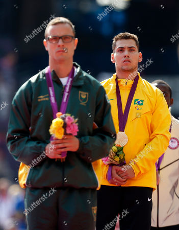 Gold medal winner Brazil's Alan Oliveira, right, stands beside silver medalist South Africa's Oscar Pistorius as he listens to his country's national anthem in the medal ceremony for the men's 200m T44 category final during the athletics competition at the 2012 Paralympics, in London. Pistorius, who won a legal battle to compete wearing carbon-fiber blades alongside able-bodied runners at the Olympics last month, suggested after the race that Oliveira ran with longer prosthesis than should be allowed