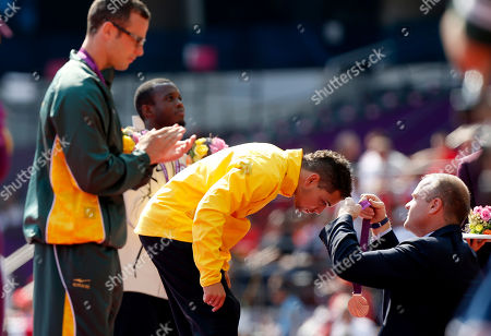 Brazil's Alan Oliveira, center, is presented with his gold medal flanked by silver medalist South Africa's Oscar Pistorius, left, in the medal ceremony for the men's 200m T44 category final during the athletics competition at the 2012 Paralympics, in London. Pistorius, who won a legal battle to compete wearing carbon-fiber blades alongside able-bodied runners at the Olympics last month, suggested after the race that Oliveira ran with longer prosthesis than should be allowed