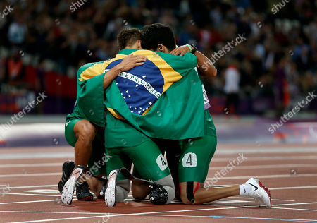 Silver medalists Brazil including Alan Fonteles Cardoso Oliveira, center, hug on the finish line draped in their flag after South Africa set a new world record of 41.78 seconds in the men's 4x100m relay T42/46 category final during the athletics competition at the 2012 Paralympics, in London