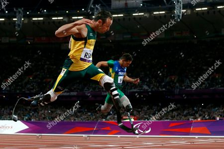 Gold medalist South Africa's Oscar Pistorius, left, sets a new world record of 41.78 seconds as he crosses the line ahead of Brazil's Alan Fonteles Cardoso Oliveira in the men's 4x100m relay T44 category final during the athletics competition at the 2012 Paralympics, in London