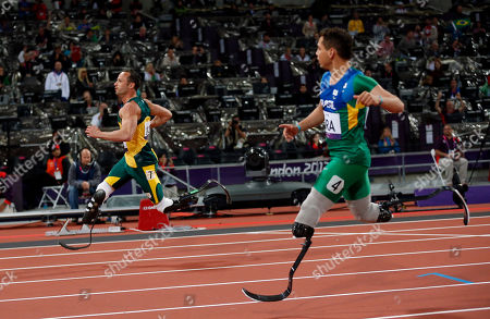 Gold medalist South Africa's Oscar Pistorius, left, runs through after crossing the line to set a new world record of 41.78 seconds ahead of Brazil's Alan Fonteles Cardoso Oliveira in the men's 4x100m relay T42/46 category final during the athletics competition at the 2012 Paralympics, in London