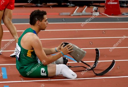 Brazil's Alan Oliveira holds one of his prosthesis after crossing the line to finish fourth in the men's 400 meters T44 category final during the athletics competition at the 2012 Paralympics, in London